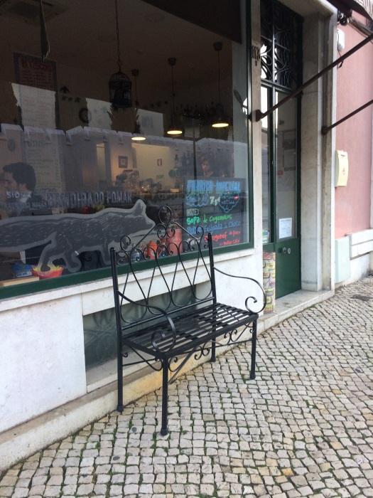 Na Rua Marquês da Fronteira um banco em ferro forjado levanta um bocadinho do pano sobre o que está lá dentro